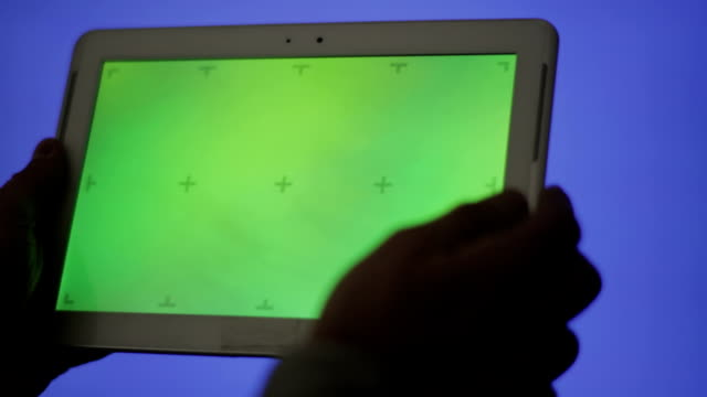 Tablet Pc on green screen against blue background. video