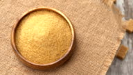 Tabletop of brown sugar rotating on burlap. Four lumps of brown sugar on rustic wooden background. Seamless loopable. Prores FullHD video