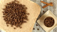 Tabletop of roasted coffee beans rotating on burlap. Rustic wooden background. Seamless loopable video