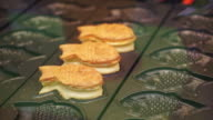 Taiyaki, Japanese traditional dessert. Pancake in bream fish shape fill with red bean or other stuff video