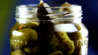 take marinated pickled cucumber from glass jar, closeup video