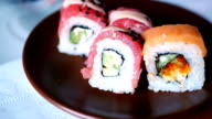 Taking three sushi rolls from plate. video