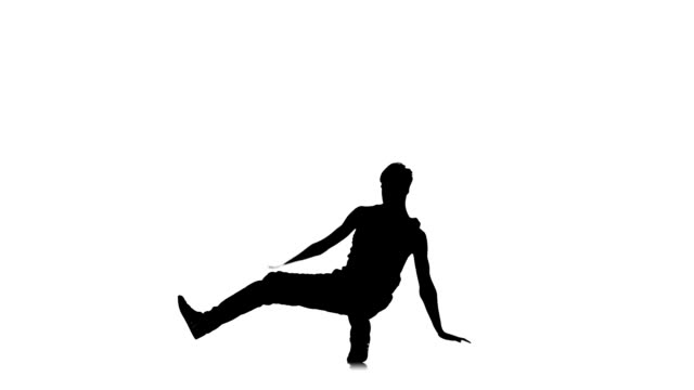 Talanted dancer dancing breakdance on hands, white, silhouette, slow motion video