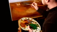 Talanted painter, dark sweater starts drawing an object on painting by oil paints holding the palette in his hand, black background, back light, close up, slow motion video