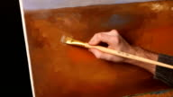 Talanted painter drawing a ground on painting by oil paints using the brush in his hand, black background, slow motion video