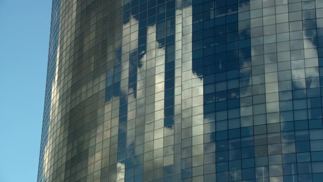 Tall mirrored skyscraper reflects the clouds going by in a timelapse video