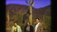1951: Tall old cactus family grudgingly posing on road trip vacation. video