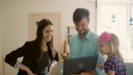 A tall young man, beautiful brunette and a cute blond little girl are watching something funny on laptop. Slow mo video