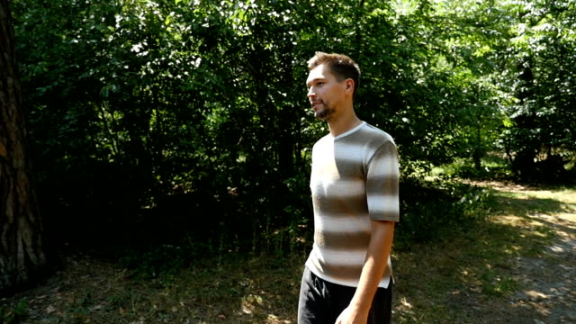 A tall young man goes freely in a green forest in summer in slow motion video
