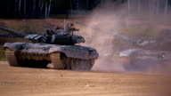 T-90 tanks are driving in a row on a ground road, stir up dust video