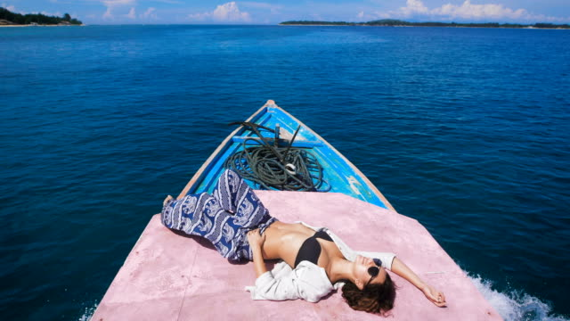 Tanned young girl in sunglasses with a thrown back arm behind her head is in the stern of the boat, which quickly goes on the dark blue ocean to a small island video