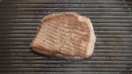 TOP VIEW: Tasty beef steak fries on a grill video