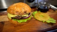 Tasty burger with cheese, lettuce, onion, tomatoes and pineapple. video