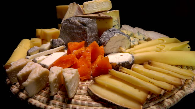 Tasty French cheeses on a plate on a black background video