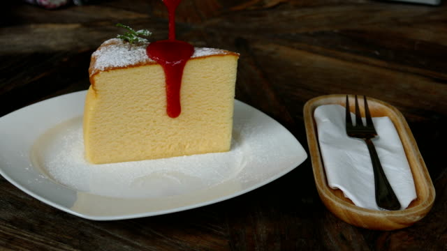 tasty strawberry sauce is poured on piece of delicious cheesecake. homemade cuisine, restaurant menus, dessert concept video