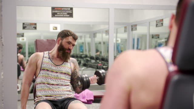 Tattooed and bearded man exercising at the gym video