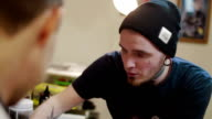 tattooist advises the client at the studio video