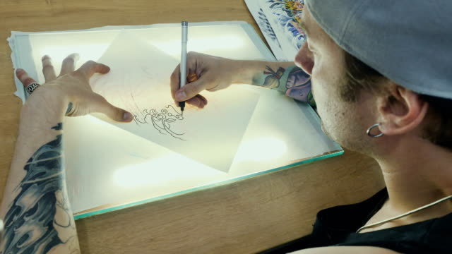 Tattooist draws the sketch on the tracing paper on the glass with light video