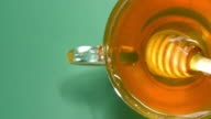 Tea cup and honey over green video