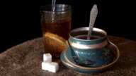 Tea is poured into the glass, the old sugar bowl and burlap on a black background video