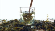 Tea leaf dissolving in hot water on white background video