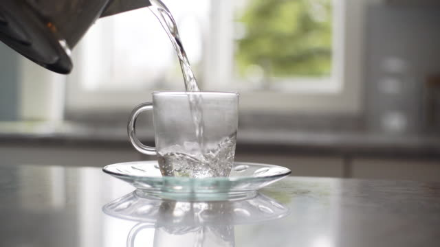 Tea preparation: pours boiled water from teapot into cup video