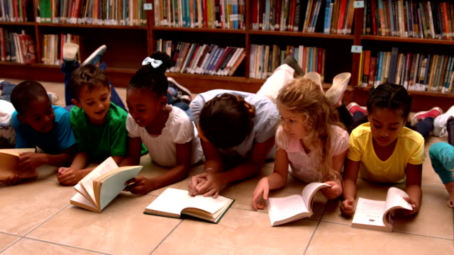Teacher and pupils reading books on library floor video