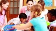 Teacher and pupils working at desk together video