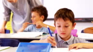Teacher assisting boy writing on notebook video