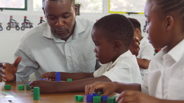 Teacher helping elementary school boy counting with blocks video