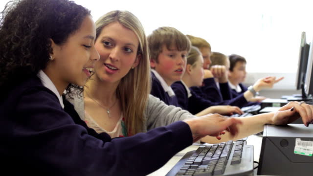 Teacher Helping Female Pupil In Computer Class video