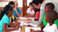Teacher helping her pupils during class video