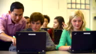 Teacher Helping High School Students Using Laptops In Class video