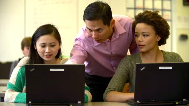 Teacher Helping High School Students Using Laptops In Class video