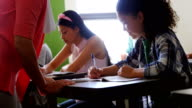 Teacher helping students with their homework in classroom video