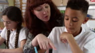 Teacher Helps Male Pupil With Work In Classroom Shot On R3D video