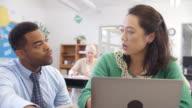 Teacher helps woman using laptop at an adult education class video