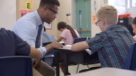 Teacher kneeling to help a 5th grade schoolboy at his desk video