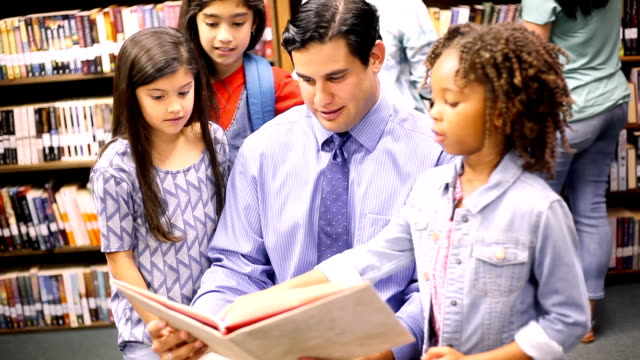 Teacher, librarian reads book to elementary students in library or classroom. video