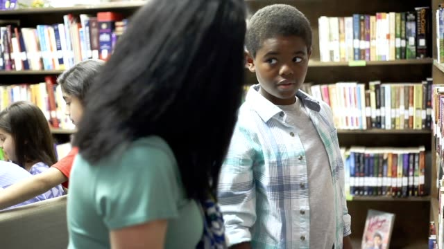 Teacher, mentor helps elementary-age boy select library book video