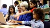 Teacher, mentor helps elementary-age school children with homework. video
