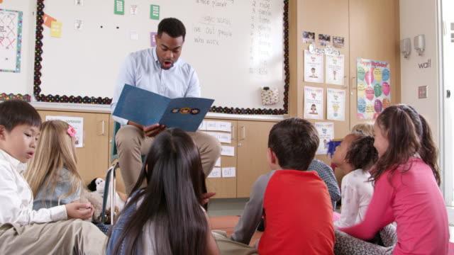 Teacher reading kids a story in an elementary school class video