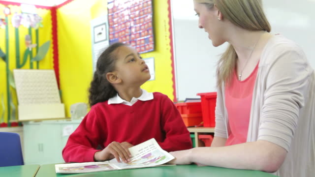 Teacher Reading With Female Pupil At Desk video
