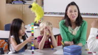 Teacher sits with kids using blocks in class, shot on R3D video