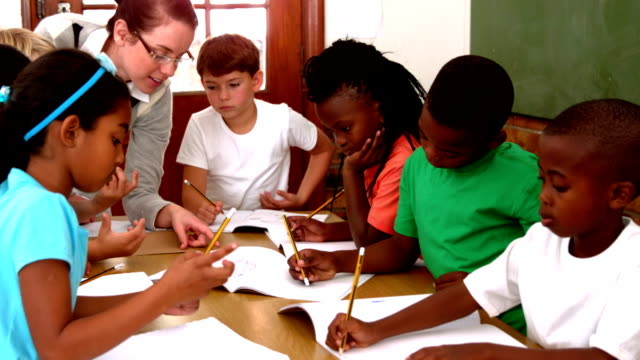 Teacher talking to her enthusiastic pupils writing in notepads video