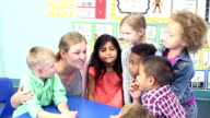 Teacher talking with her class of young school children video