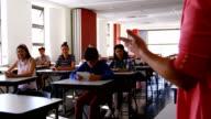 Teacher teaching students on digital tablet in classroom video