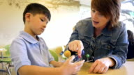 Teacher using solar system model to teach elementary age Asian boy in private school video
