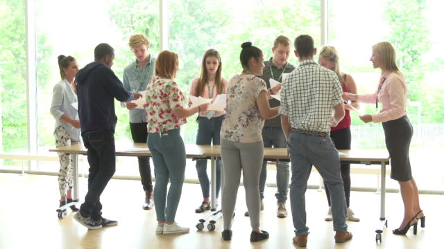 Teacher With College Students Standing By Desks In Classroom video