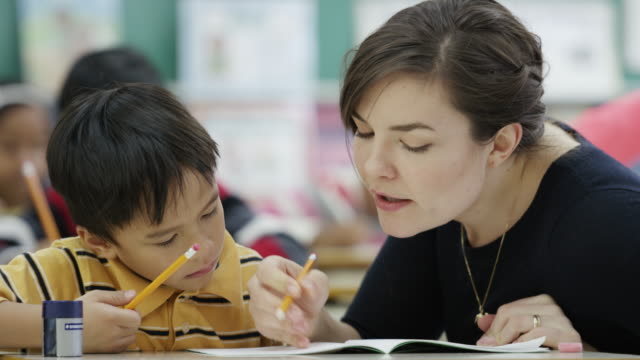 Teacher works with her elementary school students in class video
